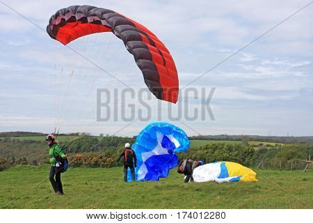Paragliders preparing to launch their wings for flight