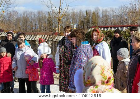 Saint-Petersburg Russia - March 13 2016: Shrovetide festivities pancake week. Adults and children celebrate end of winter and beginning of spring Mardi Gras celebration outdoors on snowy meadow. Funny Nicholas Fortress
