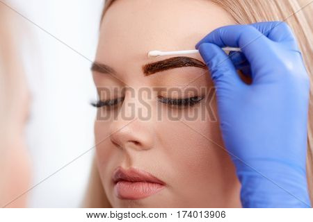 Cosmetologist cleaning face of client during permanent make up of eyebrows, using cotton buds . Professional making procedure in blue gloves for client in beauty salon.
