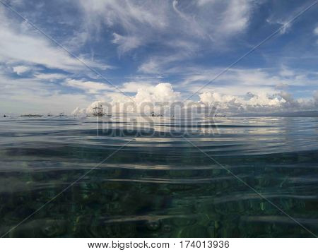 Sea and sky landscape. Above waterline. Marine double background. Seaside image. Above and below waterline. White fluffy clouds card. Ocean ripple. Seawater closeup. Banner template with text place