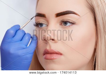Cosmetologist in blue gloves applying special permanent make up of eyebrows for attractive blonde woman. Professional making permanent eyebrows using brown paint  and brush.