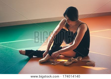 young woman dancer putting on ballet shoes prepare for training indoor shot