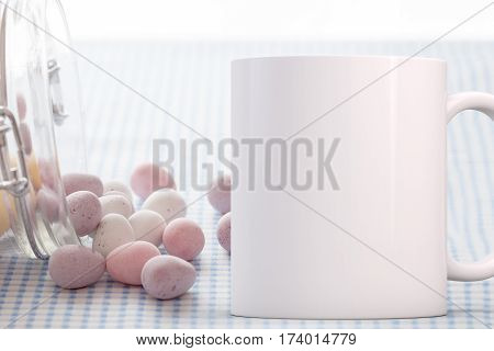 Easter Mug Mockup. Coffee Mug mockup next to chocolate mini eggs in a glass jar tipped over. Perfect for Easter mugs.