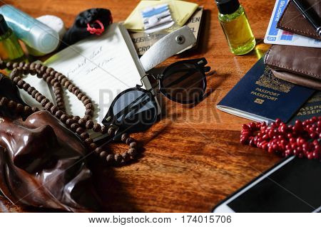 Travel background image of travel items ready to pack for adventure trip or vacation conceptual - on wooden desk with notebook, passport, sewing kit, travel sized shampoos, and other items
