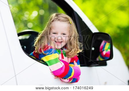 Little girl with funny pigtails watching out of car window sitting on front driver seat during a break on a family vacation road trip on summer day. Child in white minivan. Traveling by car with kids.