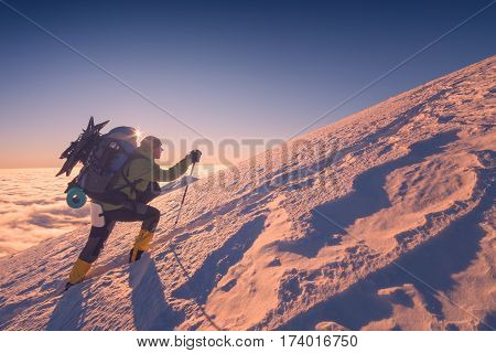 A climber with backpack climbs up a snowy mountain hill. Sunset sky on a horison.