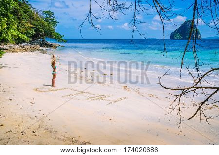 Women inscribed Help on the beach with waves and Rock in the background on a hot sunny day, El Nido, Palawan, Philippines.