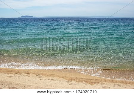 Yellow sand footprint and an emerald sea water on the beach of the Greek peninsula of Halkidiki.