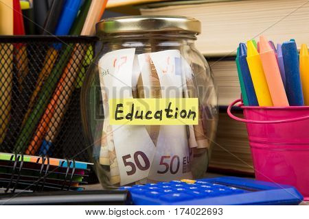 School Supplies And Glass Jar With Money For Education On Wooden Table