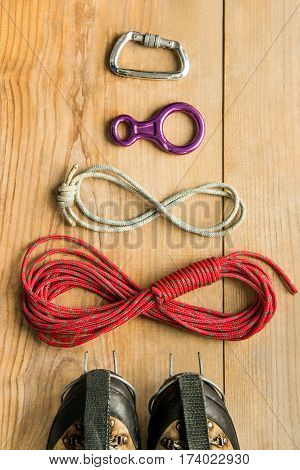 climbing equipment: rope, trekking shoes, ice tools, crampons, eight, carbine on wooden background, top view