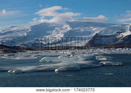 View of mountains and floating glacial ice on Jokulsarlon Lagoon, under the Vatnajokull glacier in a National Park in Iceland.
