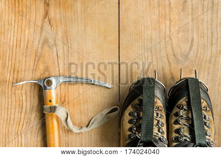 climbing equipment: trekking shoes, ice tools, ice ax, crampons on wooden background, top view