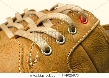 close-up view of lacing on tan color leather sneakers isolated on white background