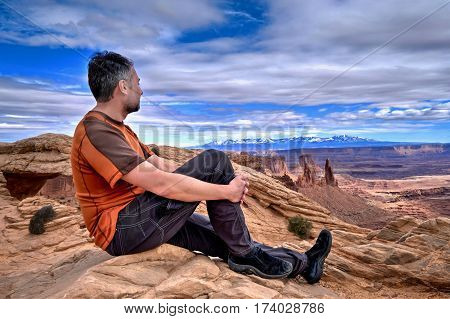 Bearded man hipster on cliff looking at canyon views. Mesa Arch in Canyonlands National Park. La Sal Mountains. Moab. Cedar City. Utah. United States.