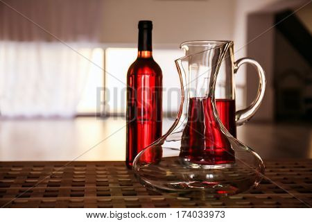 Glass carafe of wine on table against blurred background