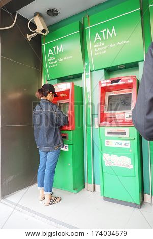 Female doing at automatic teller machine On top has close circuit television At Kasikorn Bank ATM of intersection Kaset the city of Bangkok Thailand 2017March 1 4:07P.M