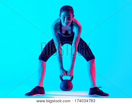 one mixed races woman exercsing Kettle Bell fitness exercices isolated on blue blackground