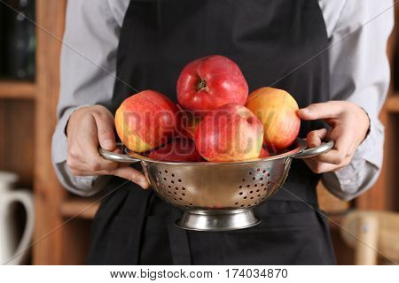 Woman in apron holding colander with juicy apples, closeup