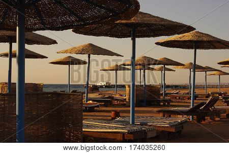 Beach with deckchairs and umbrellas on a sunset.