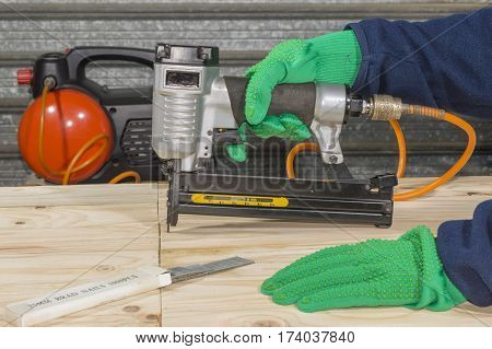 A carpenter uses a pneumatic staple gun