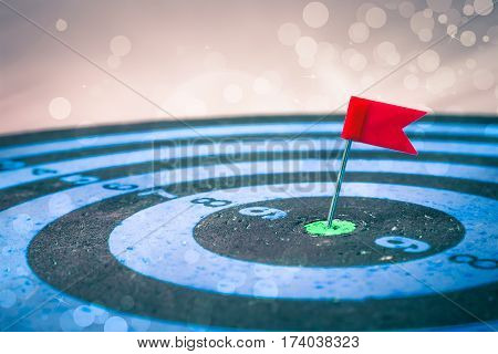 Smart goal setting, red pin hit the center of dartboard with light backdrop on background.  target concept