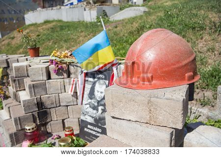 KIEV UKRAINE - AUGUST 8 2015: Memorial erected to the people killed by snipers on Heroyiv Nebesnoyi Sotni street during the Euromaidan revolution and protests on Maidan Square - Independence Square with a ukrainian flag on it