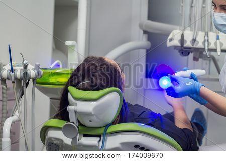 Dentist preparing ultraviolet light before making dental fillings. Stong UV light.