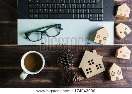 Top View Of Office Stuff With Laptop Coffee Cup And Wooden House Toy On Wooden Table.concept Workpla