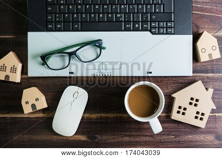 Top View Of Office Stuff With Laptop Wireless Mouse Coffee Cup And Wooden House Toy On Wooden Table.