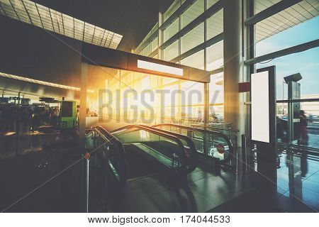 Moving staircase inside of modern airport terminal hall with multiple passengers waiting their flights interior of airport with escalator going down huge window with cabstand and cars outside