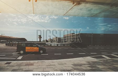 Yellow taxi on the road in front of air traffic control tower of modern contemporary airport terminal of Barcelona with buses and multiple moving blurred cars in distance on sunny day