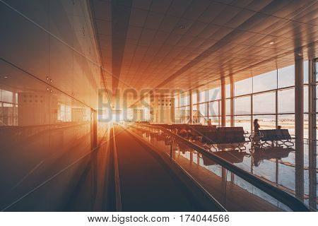 Moving walkway in modern airport terminal of Barcelona travelator in waiting hall with empty seats with several people waiting their aircraft big windows and reflective floor flare in the end of way