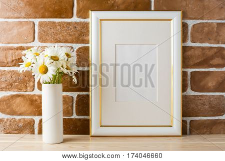 Gold decorated frame mockup with daisy bouquet in styled vase near exposed brick wall. Empty frame mock up for presentation design. Template framing for modern art.