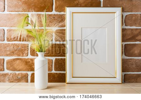 Gold decorated frame mockup with ornamental grass in styled vase near exposed brick wall. Empty frame mock up for presentation design. Template framing for modern art.