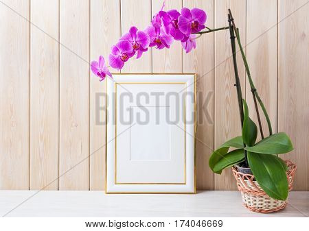 Gold decorated frame mockup with magenta-purple orchid in wicker basket near wooden wall. Empty frame mock up for presentation design. Rustic framing template for modern art.