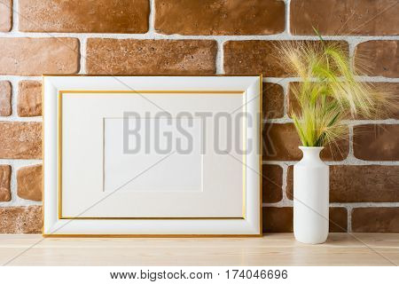 Gold decorated landscape frame mockup with ornamental grass in styled vase near exposed brick wall. Empty frame mock up for presentation design. Template framing for modern art.