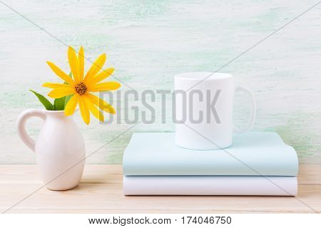 White coffee mug mockup with golden yellow rosinweed in pitcher. Empty mug mock up for brand promotion.