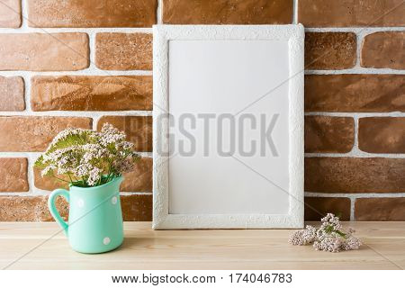 White frame mockup with wild creamy pink flowers in mint pitcher near exposed brick wall. Empty frame mock up for presentation design. Template framing for modern art.