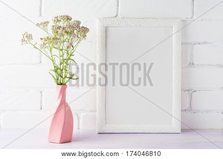White frame mockup with creamy pink flowers in swirled vase. Empty frame mock up for presentation design.