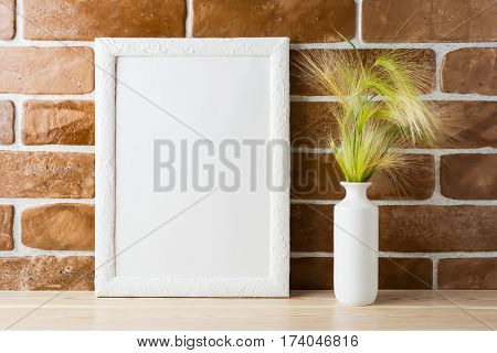 White frame mockup with ornamental grass in styled vase near exposed brick wall. Empty frame mock up for presentation design. Template framing for modern art.