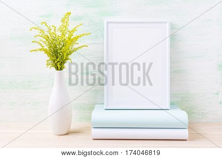 White frame mockup with wild ornamental green grass and books. Empty frame mock up for presentation design. Template framing for modern art.