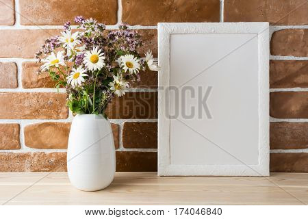 White frame mockup with wild wildflowers bouquet in in styled vase near exposed brick wall. Empty frame mock up for presentation design. Template framing for modern art.
