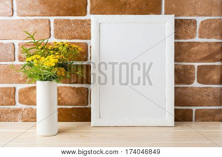 White frame mockup with wild rich golden yellow flowers in vase near exposed brick walls. Empty frame mock up for presentation design. Template framing for modern art.