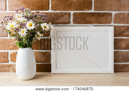 White landscape frame mockup with wwildflowers bouquet in styled vase near exposed brick wall. Empty frame mock up for presentation design. Template framing for modern art.