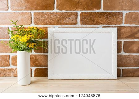 White landscape frame mockup with wild rich golden yellow flowers in vase near exposed brick walls. Empty frame mock up for presentation design. Template framing for modern art.
