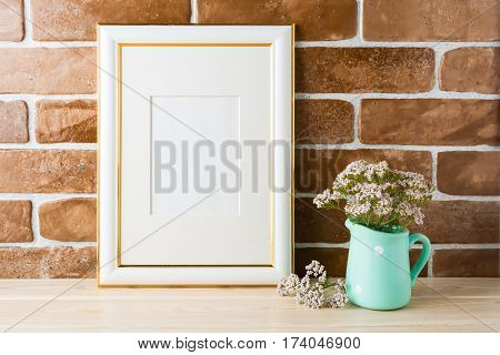 Gold decorated frame mockup with wild very soft pink flowers in mint pitcher near exposed brick wall. Empty frame mock up for presentation design. Template framing for modern art.