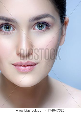 beauty closeup portrait of attractive young  caucasian woman brunette on blue background studio shot lips face skin care  looking at camera