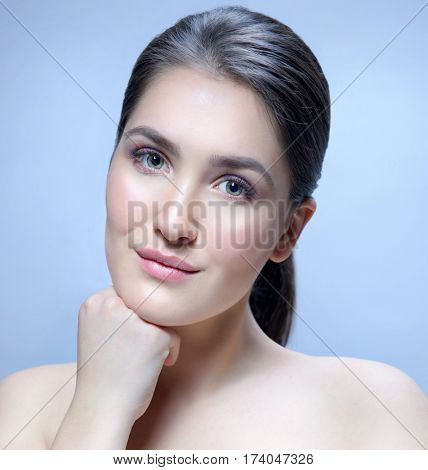 Beauty Spa Woman with Perfect skin Portrait. Beautiful Brunette Spa Girl . Young Caucasian with Fresh looking Skin. Beauty Woman Face Closeup. Blue background. Looking at camera. Studio shot