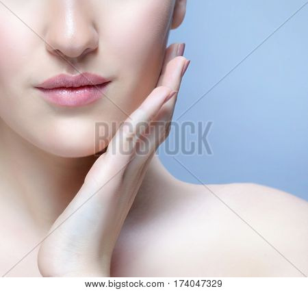 closeup portrait of attractive young  caucasian woman on blue background studio shot lips face  skin hands nails lips neck