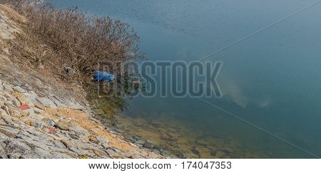 Lake in South Korea with a large blue barrel caught in the branches of a small tree in the water next to shore